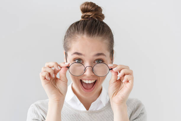 indoor portrait of excited european female with hair tied in bun isolated on grey background with stylish black-rimmed eyeglasses, her mouth open wide in surprise with positive news or good offer. - smile woman open mouth foto e immagini stock
