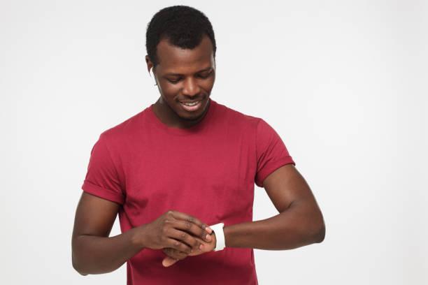 indoor-porträt von schöner afroamerikanische mann stehend vor grauen hintergrund in rot lässigen t-shirts anpassen intelligente armbanduhr trägt er um es ohne probleme während der anstrengenden aktiv tag verwenden - geek t shirts stock-fotos und bilder
