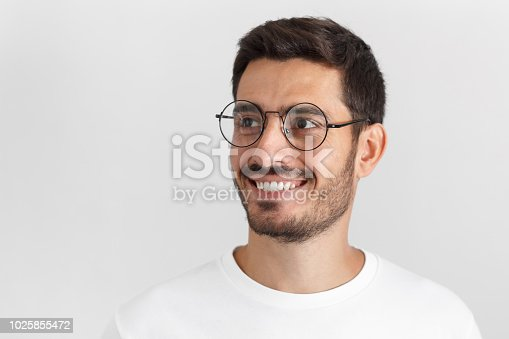 istock Indoor portrait of handsome young european caucasian man isolated on gray background, dressed in casual white t-shirt, wearing round glasses, having turned aside as if looking at something 1025855472