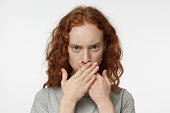 Indoor portrait of teenage European girl with red hair pictured isolated on white background, hiding her mouth behind hands in resolute gesture refusing to reveal secrets and share confidential data