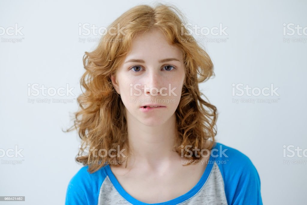 Indoor portrait of young beautiful redhead European female isolated on white background wearing blue T-shirt royalty-free stock photo