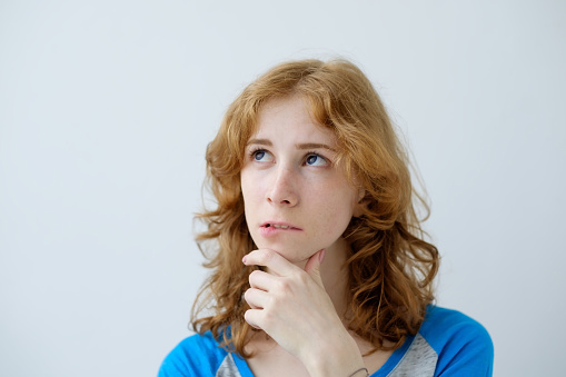 젊은 아름 다운 빨간 머리 유럽 여성 파란 T셔츠를 입고 흰색 배경에 고립의 실내 초상화 결정에 대한 스톡 사진 및 기타 이미지