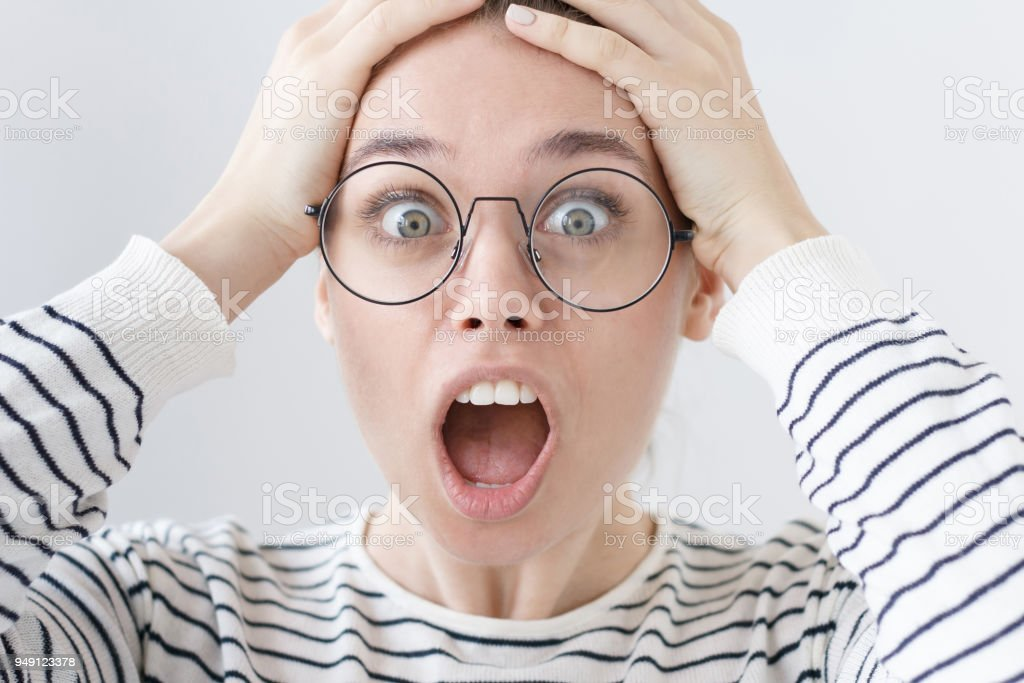 Indoor portrait of young European female in casual clothes and glasses isolated on grey background screaming desperately with expression of deep shock as if she heard unbelievable surprising news. stock photo