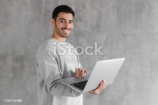947303582 istock photo Indoor portrait of young man in gray sweatshirt standing against textured wall, holding laptop and looking at camera with happy smile 1125110769
