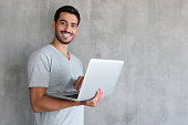 Indoor portrait of young man in t shirt standing against textured wall with copy space for ads, holding laptop and looking at camera with happy smile
