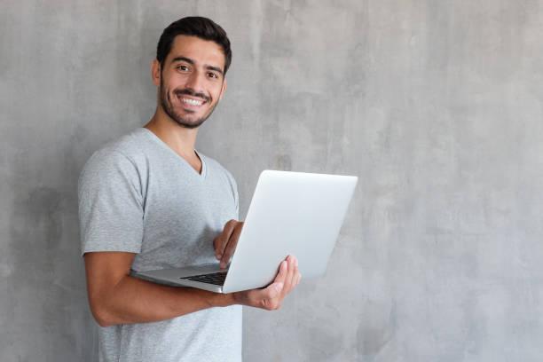 indoor-porträt von junger mann in t-shirt gegen strukturierte wand mit textfreiraum für anzeigen, laptop halten und blick in die kamera mit glücklichen lächeln - junger mann stock-fotos und bilder