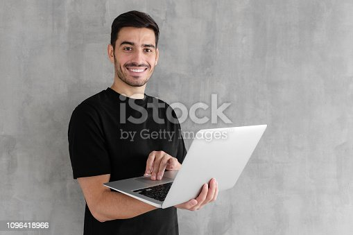 947303582 istock photo Indoor portrait of young man in t-shirt standing against textured wall, holding laptop and looking at camera with happy smile 1096418966