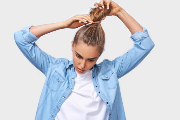 Indoor portrait of young woman collecting hair in a ponytail, wearing blue denim shirt and white t-shirt, posing over white wall. Adorable blonde female makes ponytail, advertises healthy natural hair stock photo