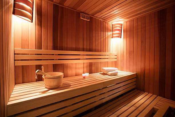 Sauna interior Sauna interior. Sauna is ready to receive guests. Towel are rolled, and candles lighted. Photo made with available light, and with very nice warm tones.   sauna stock pictures, royalty-free photos & images