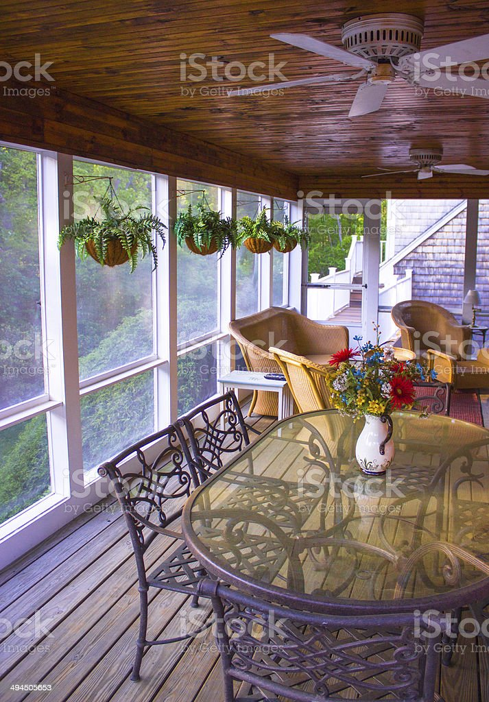 Indoor Screened In Porch with plants & chairs & tables stock photo