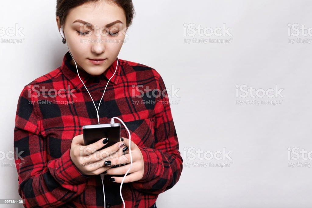 Tiro indoor de garota atraente jovem hippie vestido casual camisa ouvir audiobook ou rádio no celular com fones de ouvido. Conceito de música e tecnologia. - foto de acervo