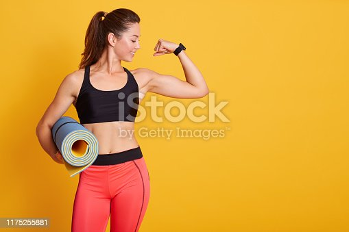 istock Indoor shot of woman raises arm and showing muscles after training, holding karemat, like to workout in gym with coach, dresses stylish sportswear, isolated over yellow studio wall. Strength concept. 1175255881