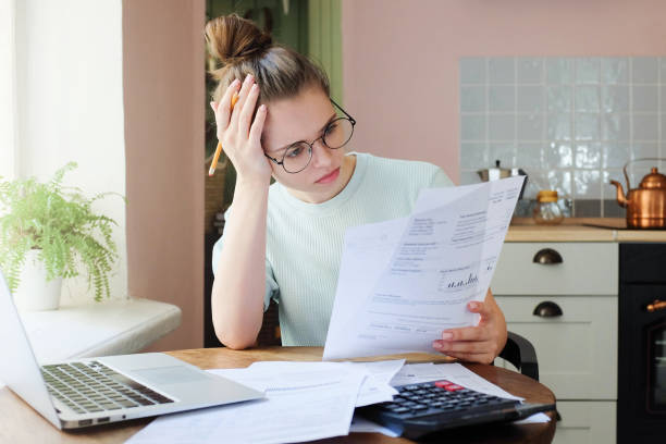 indoor shot of young european caucasian girl looking at financia - bills and taxes stock pictures, royalty-free photos & images