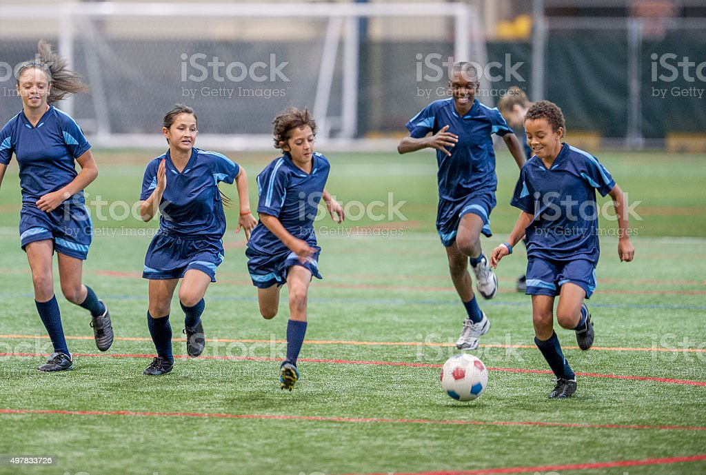 A multi-ethnic group of elementary age children are running up the...
