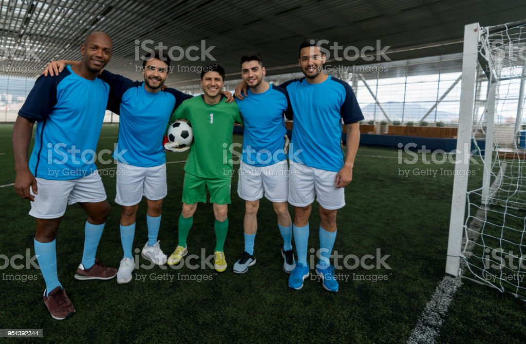 Indoor soccer male team looking at camera smiling very happy while...