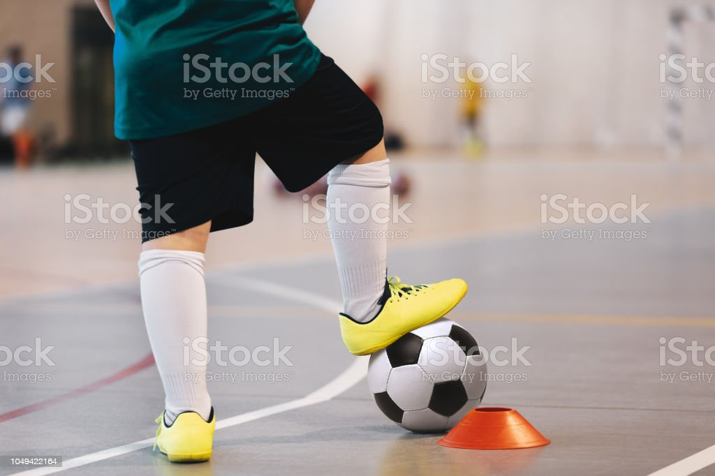 Indoor soccer player training with balls. Indoor soccer sports hall....