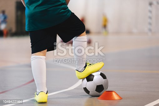 istock Indoor soccer player training with balls. Indoor soccer sports hall. Football futsal player, ball, futsal floor. Sports background. Futsal league. Indoor football players with classic soccer ball. 1049422164