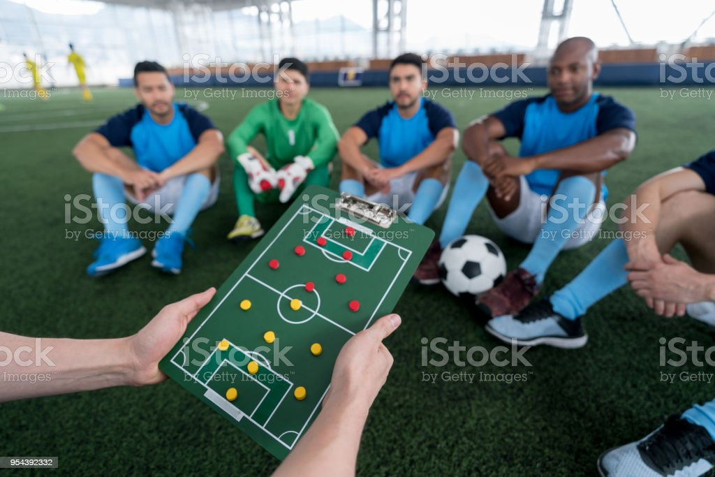 Indoor soccer players looking at the coach who is holding a clipboard...