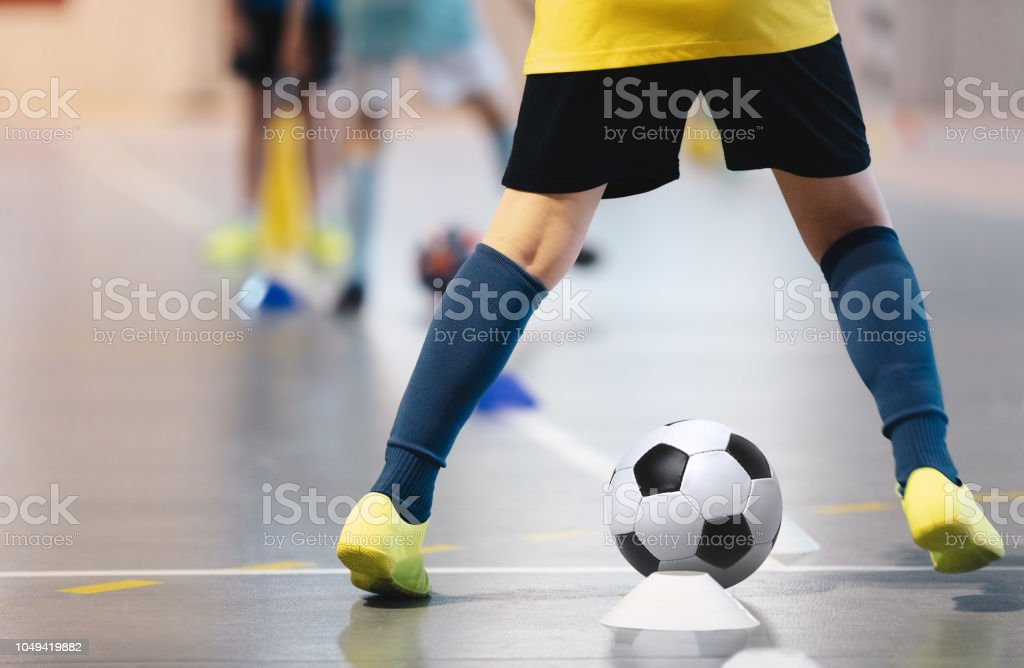 Indoor soccer players training with balls. Indoor soccer sports hall....