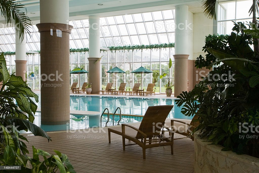 Indoor swimming pool at resort A view into an indoor swimming pool at a luxury resort hotel in Okinawa, Japan with tropical plants in the foreground (unsharpened). Asia Stock Photo