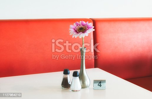 Indoor table setting in a cafe with flower in pot, salt and pepper shakers and metal number marker