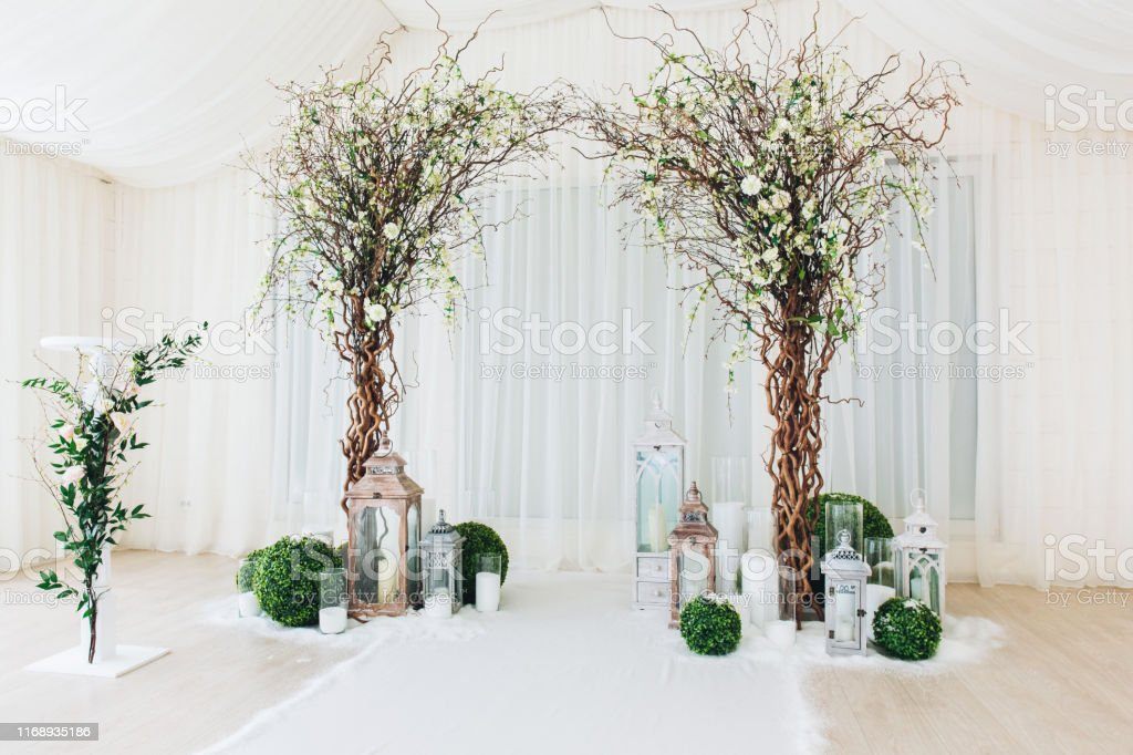 Indoor Wedding Ceremony With White Wedding Arch Decorated With