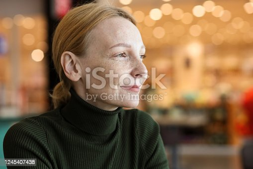 indoors portrait of a 45 year old red-haired woman with freckles in a green sweater