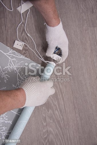 Indoors repair of premises. Repair and interior design. Male hands of a worker in white gloves prepare the roller blinds for installation. Parts and tools