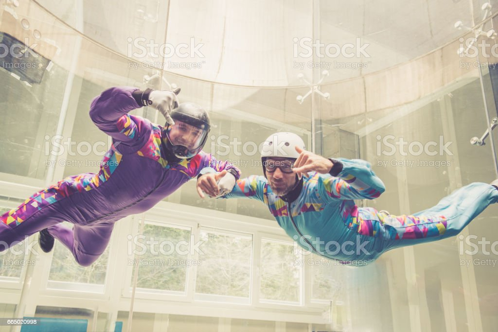 Indoors skydiving -instructor teaching how to fly - freefall simulation - posing stock photo