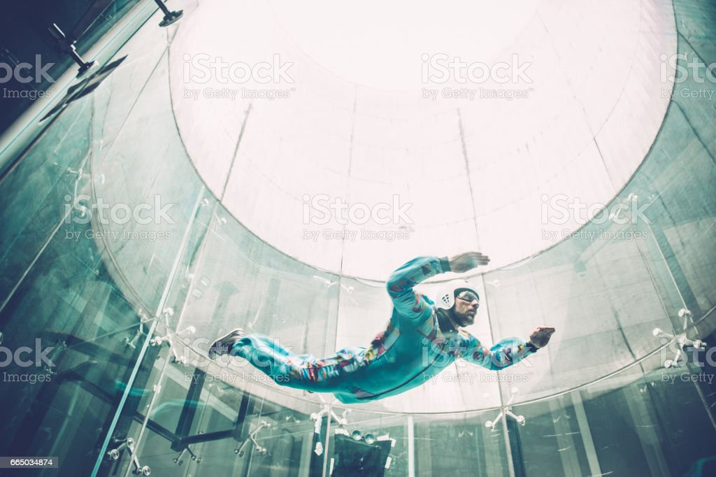 Indoors skydiving - one young man practising freefall simulation stock photo