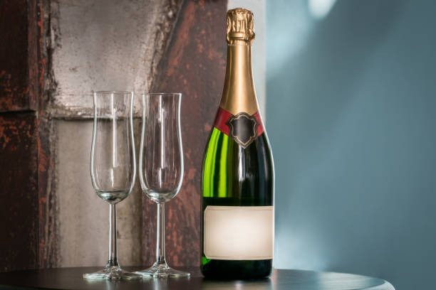 Indoors still life shot of a unopened champagne bottle and two empty glasses on a table. Label with copy space. stock photo