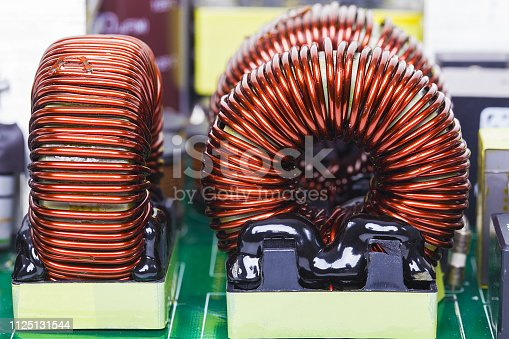 Fragment of a powerful power supply circuit, inductance coil close-up .