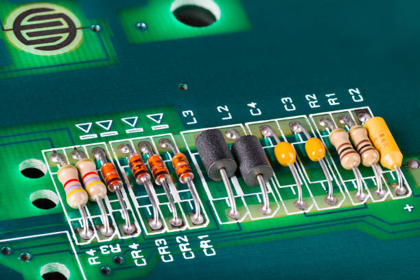 Inductors, capacitors, resistors and diodes on green PCB. Black coils. stock photo