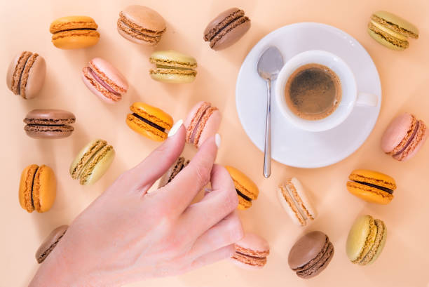 Indulge yourself - Macaroons and a espresso on a pastel background with a hand stock photo