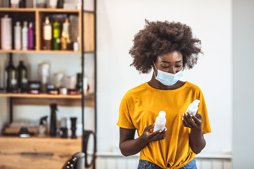 Photo of African american young woman examining some beauty products in a salon, wearing protection face mask against corona virus