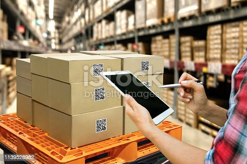 istock Industrial 4.0 , Augmented reality and smart logistic concept. Hand holding tablet with AR application for check order pick time around the world and supply chain in smart factory background. 1139528982