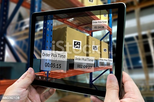 istock Industrial 4.0 , Augmented reality and smart logistic concept. Hand holding tablet with AR application for check order pick time in smart factory background 680262128