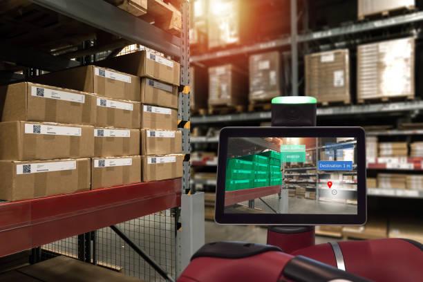 Industrial 4,0, realidad aumentada y concepto logístico inteligente. Robot asesor con la aplicación de AR para el tiempo de selección de pedido de cheques en el almacén industrial de fábrica inteligente. - foto de stock