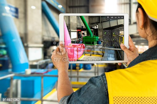 istock Industrial 4.0 , Augmented reality concept. Hand holding tablet with AR service , maintenance application and calling technician for check destroy part of smart machine in smart factory background. 914921062