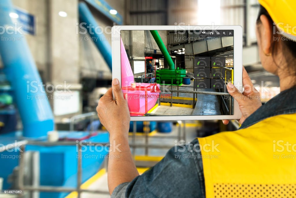 Industrial 4.0 , Augmented reality concept. Hand holding tablet with AR service , maintenance application and calling technician for check destroy part of smart machine in smart factory background. stock photo