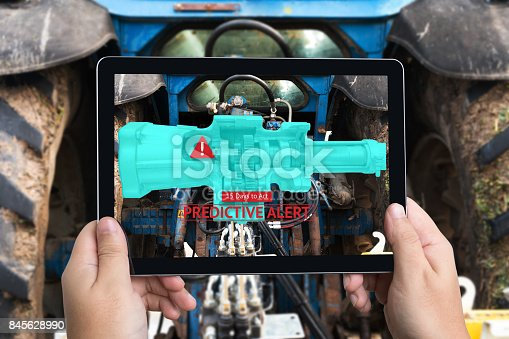 istock Industrial 4.0 , Augmented reality technology , smart agriculture and farm concept. Hand holding tablet with AR maintenance application and predictive alert for check destroy part of smart machine. 845628990