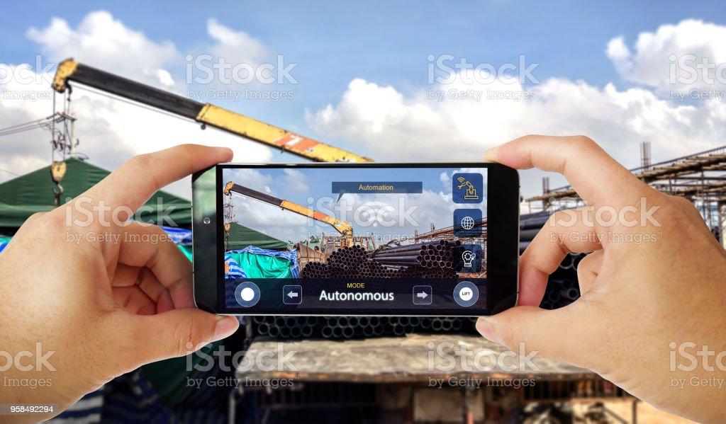 Industrielle 4.0 IOT-Konzept, Mann Kontrolle autonomer LKW-Kran mit Anwendung auf Smartphone. Smart-Logistik-Branche. – Foto