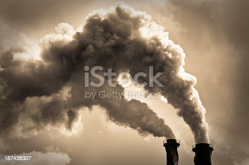 Toned monchrome image with billowing smoke coming from two chimneys.  Please note that limited film grain has been added during image processing.