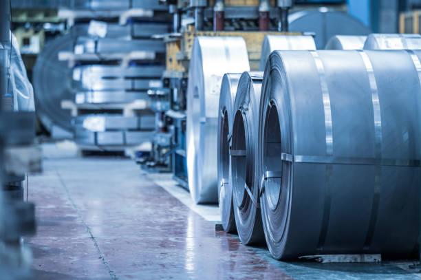 industriële achtergrond. grote grootte stalen spoel opgeslagen in industriële magazijn, blauw afgezwakt beeld. - legering stockfoto's en -beelden