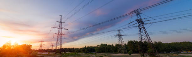 Industrial background of silhouette of transmission tower, electricity pylon on red sunset background