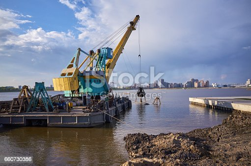 Industrial barge dredging crane work coast. Equipment engineering, reflection in water