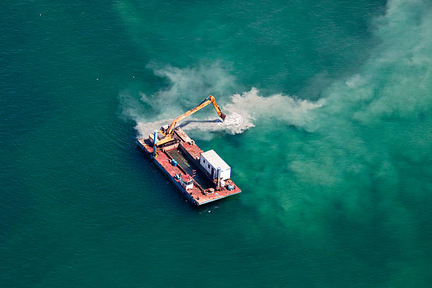 Industrial Barge with an Excavator on the Sea Industrial Barge with an Excavator on the Sea groyne stock pictures, royalty-free photos & images