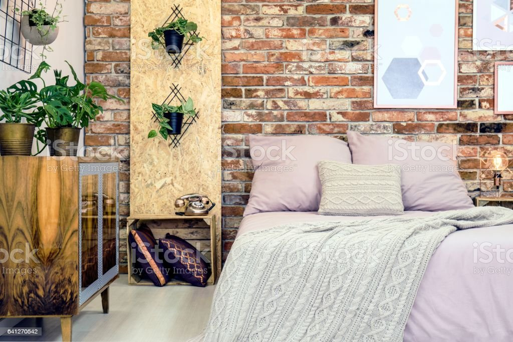 Industrial bedroom with pink bedding stock photo