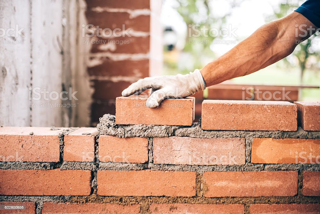 industrial bricklayer worker placing bricks on cement while building walls stock photo