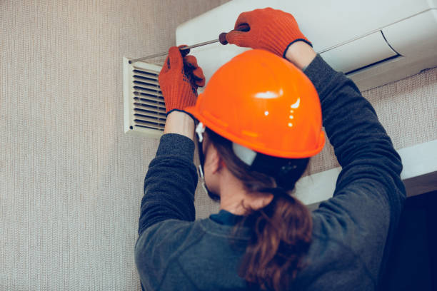 Industrial builder, handyman installing ventilation or air conditioning filter holder in wall stock photo